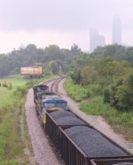 CSX 741 & 98 sit in the siding with a loaded coal train near the downtown skyline
